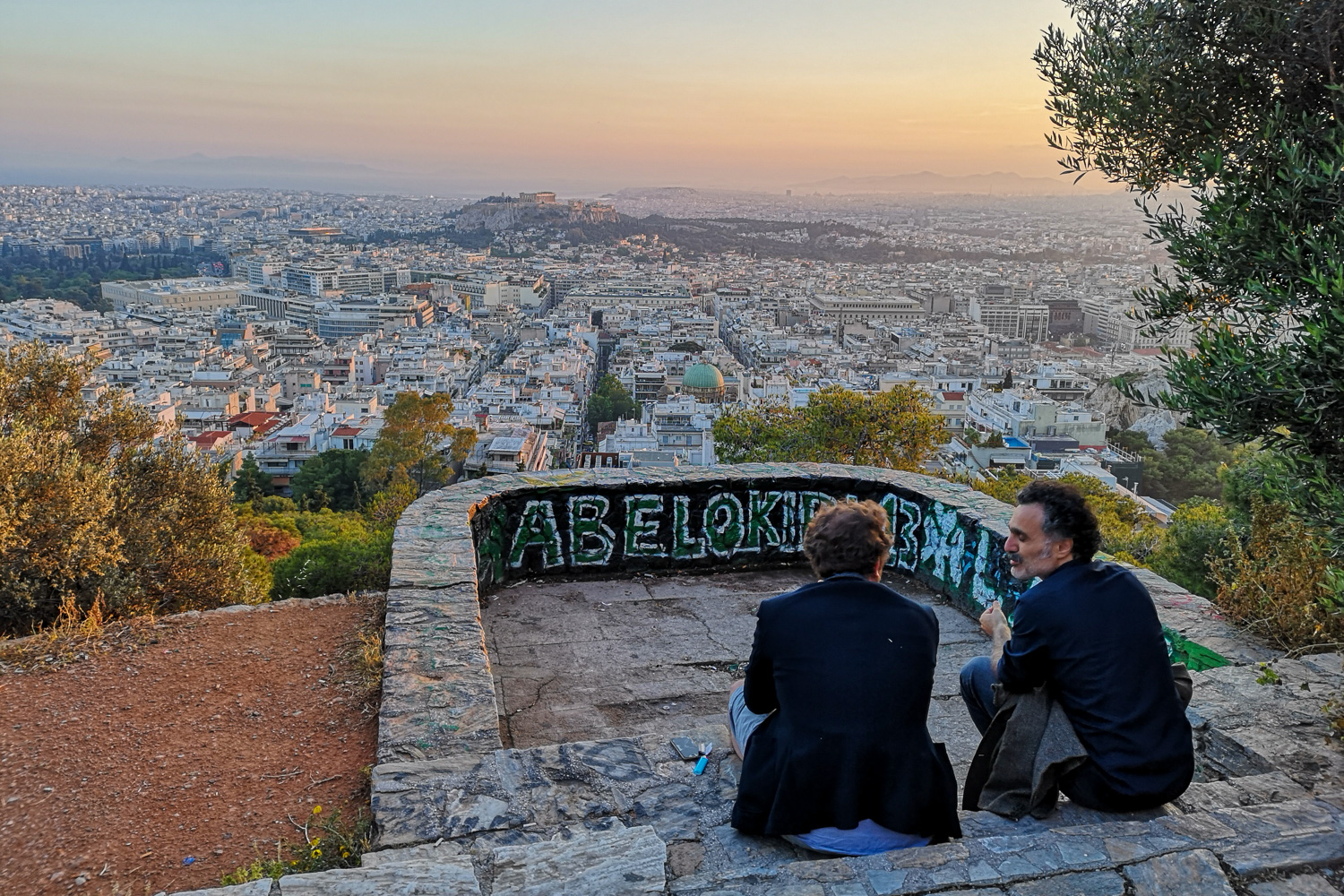 2 men enjoy a sunset on Lycabettus Hill in Athens, Greece