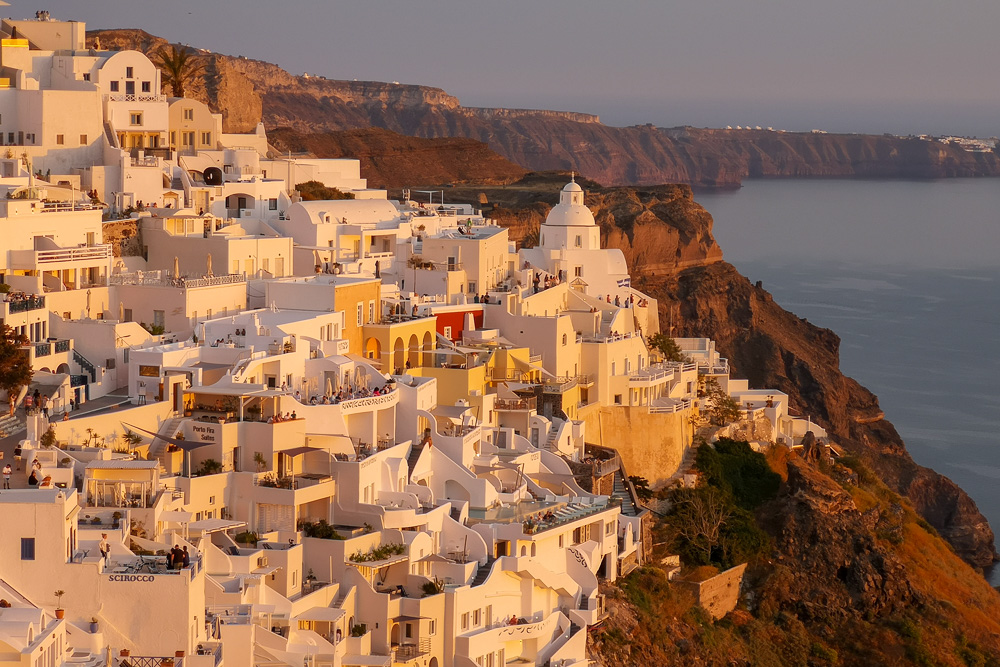 During golden hour in Fira, Greece the sun lights up the city