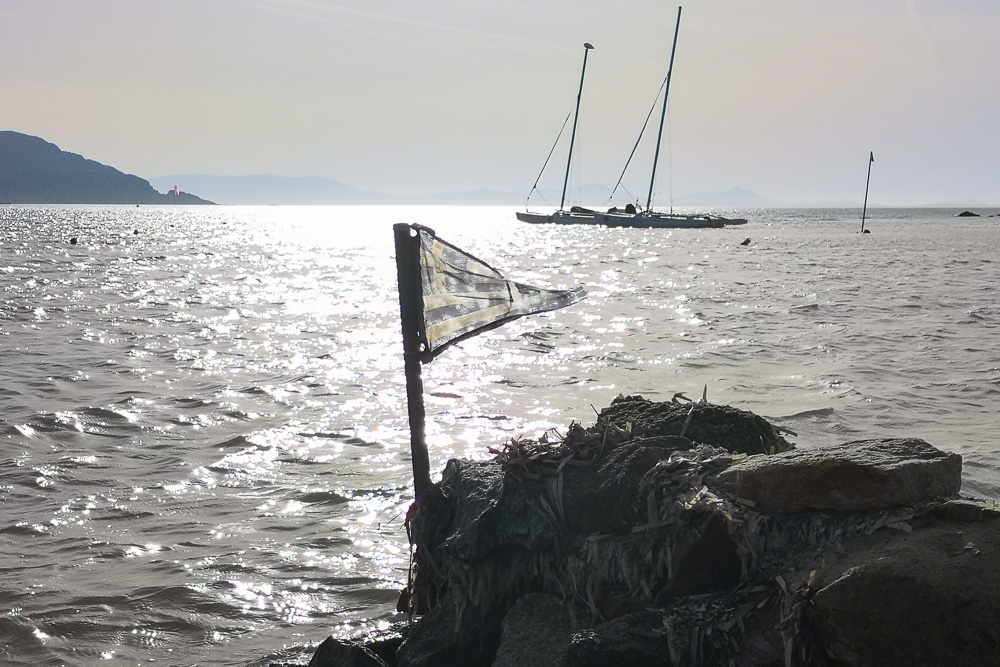 A Greece Flag with sailboats behind
