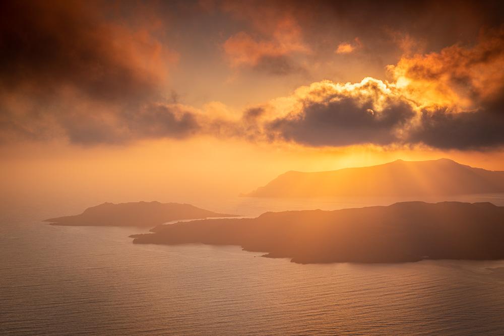 Light rays shine down at sunset in Santorini